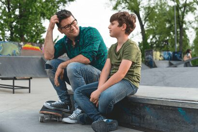 Man and child in skate park