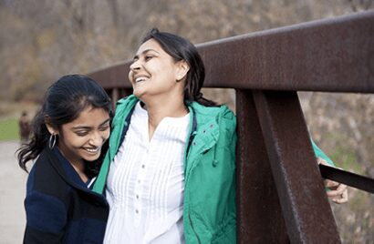 Foster mother and daughter on a bridge