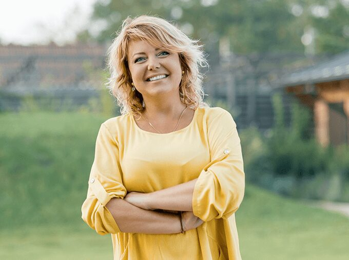 Middle-aged woman in garden wearing a yellow top