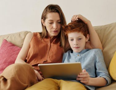 Mother and son using tablet ont he sofa