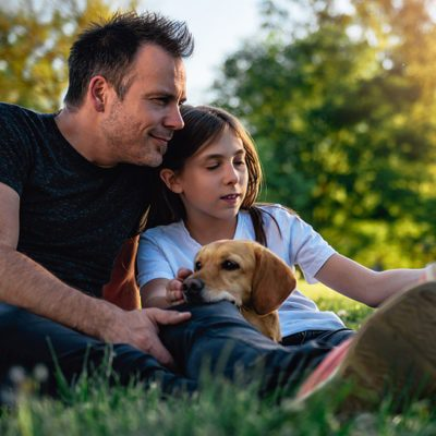 Father, daughter and dog taking selfie in the park