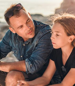 Father and daughter talking on beach