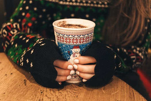 Holding cup of coffee in Christmas jumper