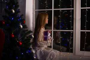 Girl looking out window at Christmas