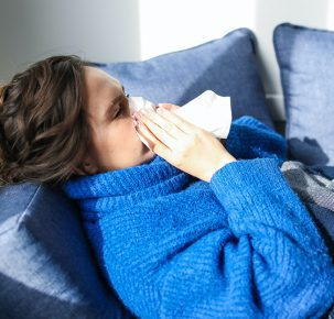 Woman blowing nose in to tissue