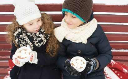 Children in snow with hot chocolate drinks