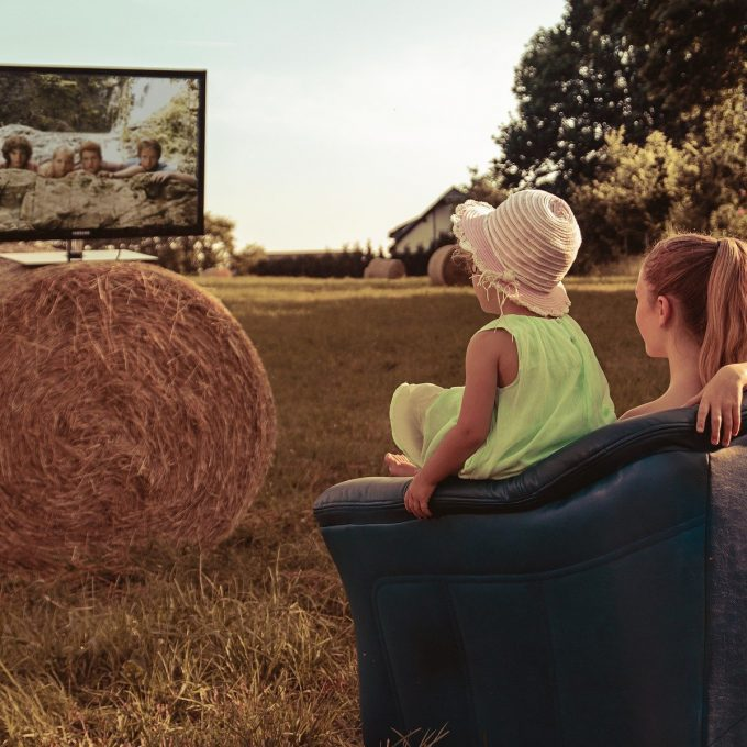 Kids watching tv on top of a haystack